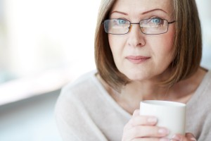 A woman with glasses holding a mug
