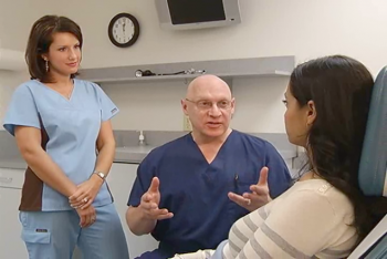 Dr. Wortman and a nurse talking with a patient.