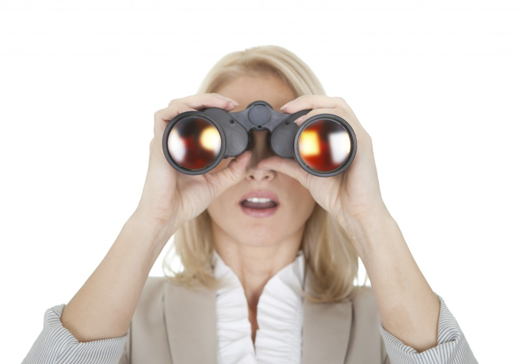 A woman looking through a pair of binoculars.